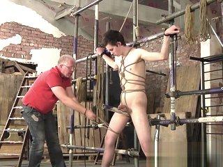 Mature master Sebastian Kane strokes his bound slaves cock
