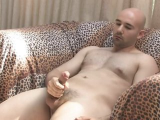Solo bald guy masturbates on couch